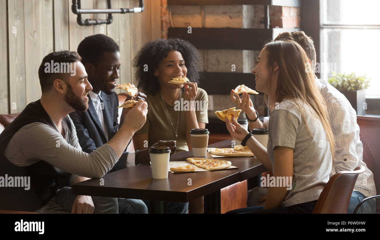 Smiling multiracial colleagues enjoying lunch spending work brea - Stock Image