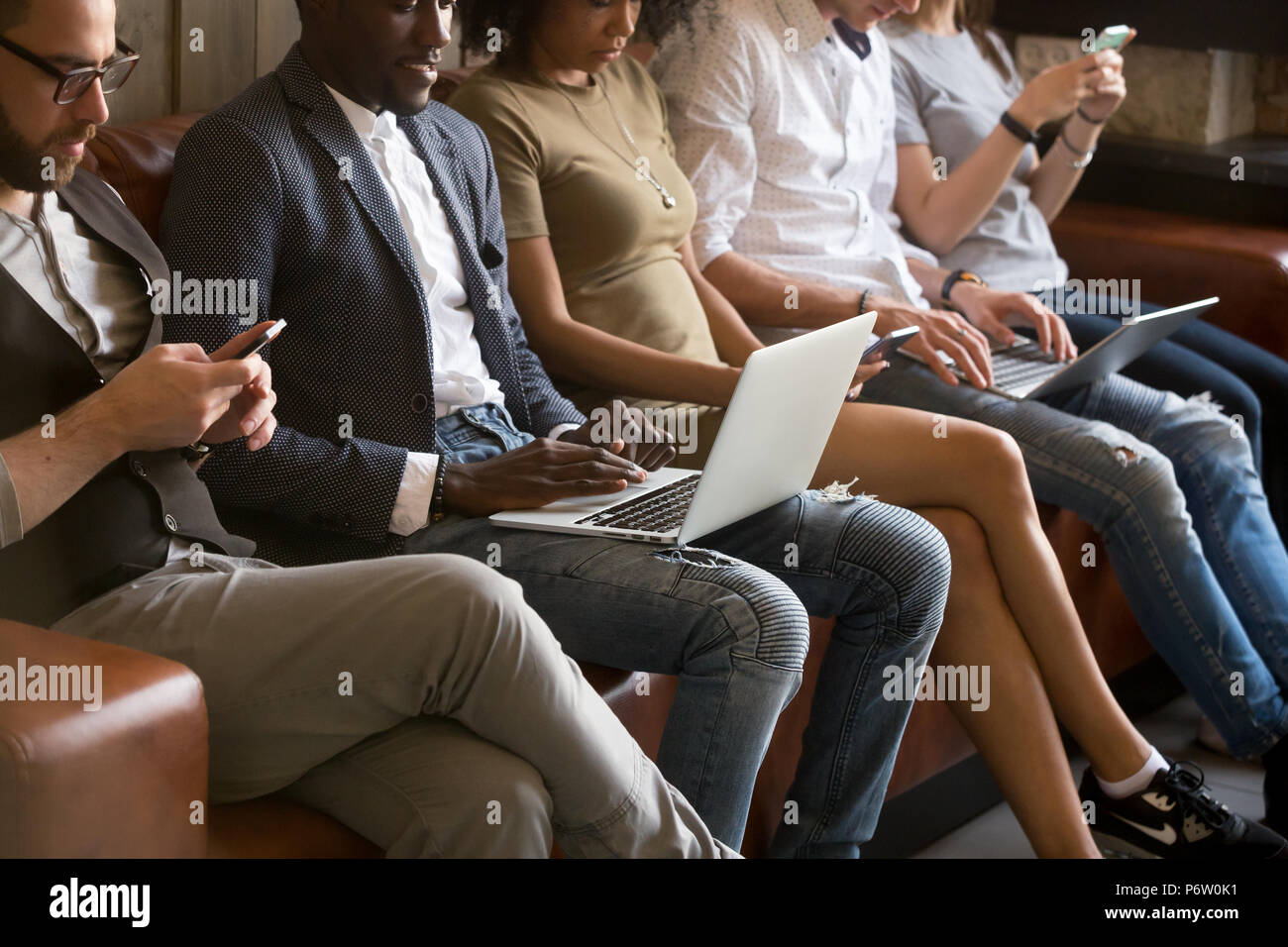 Close up of technology obsessed multiracial people sitting in qu - Stock Image
