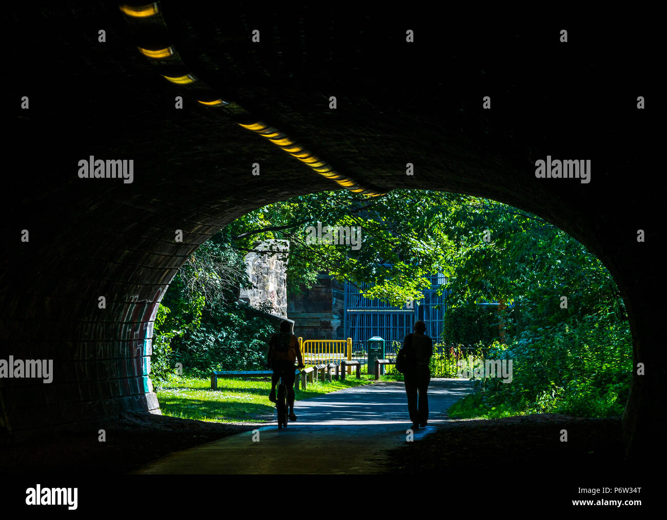Silhouettes of man walking and cyclist in entrance of disused railway tunnel with contrast of sunshine and darkness. A commuting route, Edinburgh, Scotland, UK - Stock Image