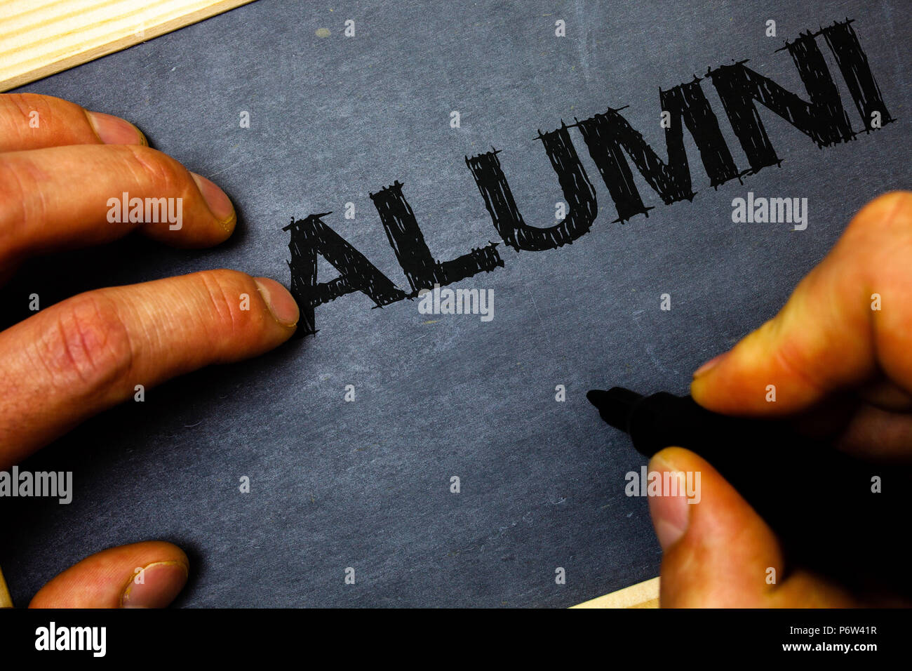 Word writing text Alumni. Business concept for Alum Old graduate Postgraduate Gathering College Academy Celebration Man hold holding black marker mark - Stock Image