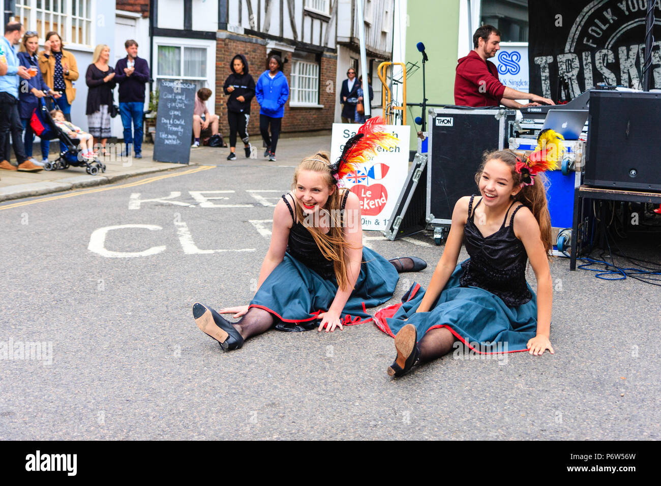 Two young women, teenage girls, performing the Can-Can in a street during a festive event. Stage with musicians behind them. Stock Photo