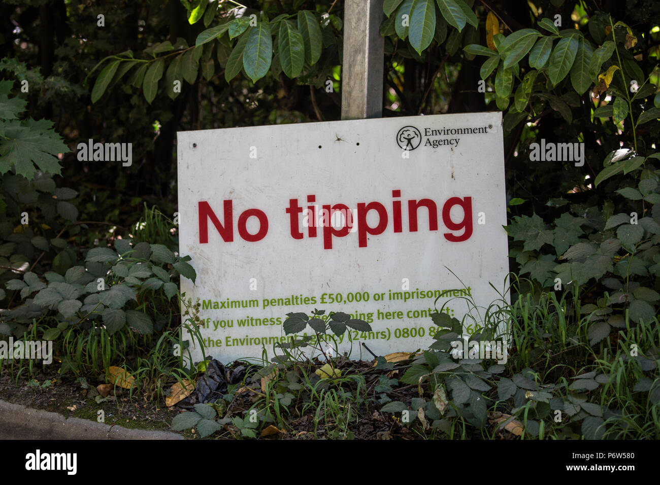 Englefield Green, UK. 2nd July, 2018. An Environment Agency sign warning against the fly-tipping, or the illegal dumping of waste. - Stock Image