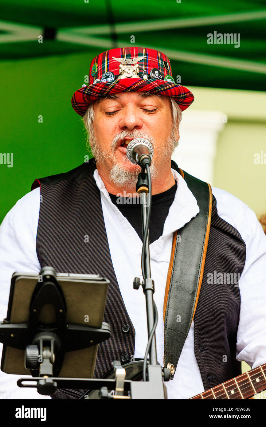 Close-up, waist up, Caucasian man, 40s, playing electric guitar at open air concert. Fred Rok of French folk rock band Triskelles singing on stage. - Stock Image