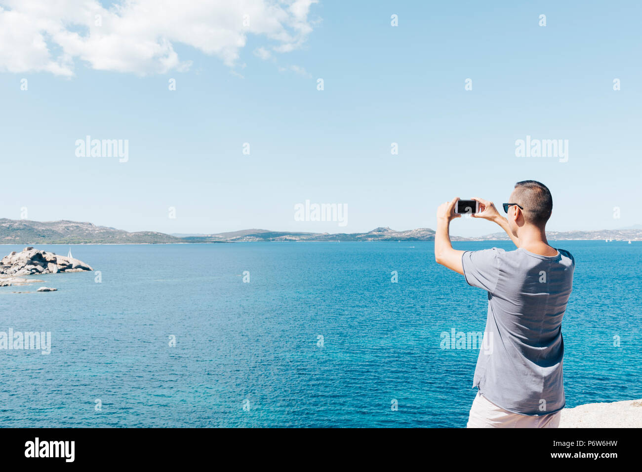 closeup of a young caucasian man seen from behind taking a photo of the sea in the Costa Smeralda, in Sardinia, Italy, with his smartphone, with a bla - Stock Image
