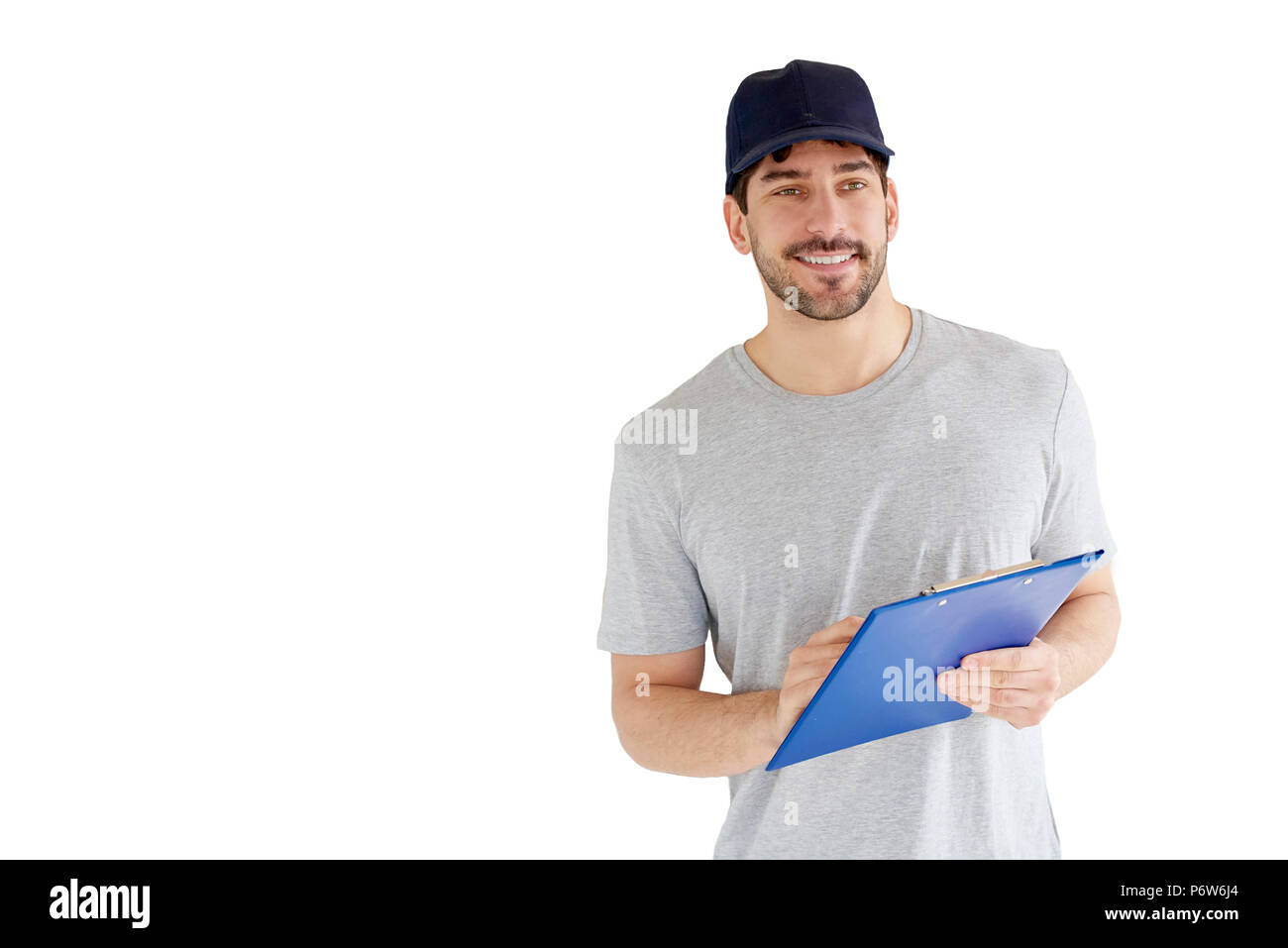 Portrait of handsome young man standing at isolated white background. Smiling carrying man wearing baseball cap and holding clipboard in his hand. Stock Photo