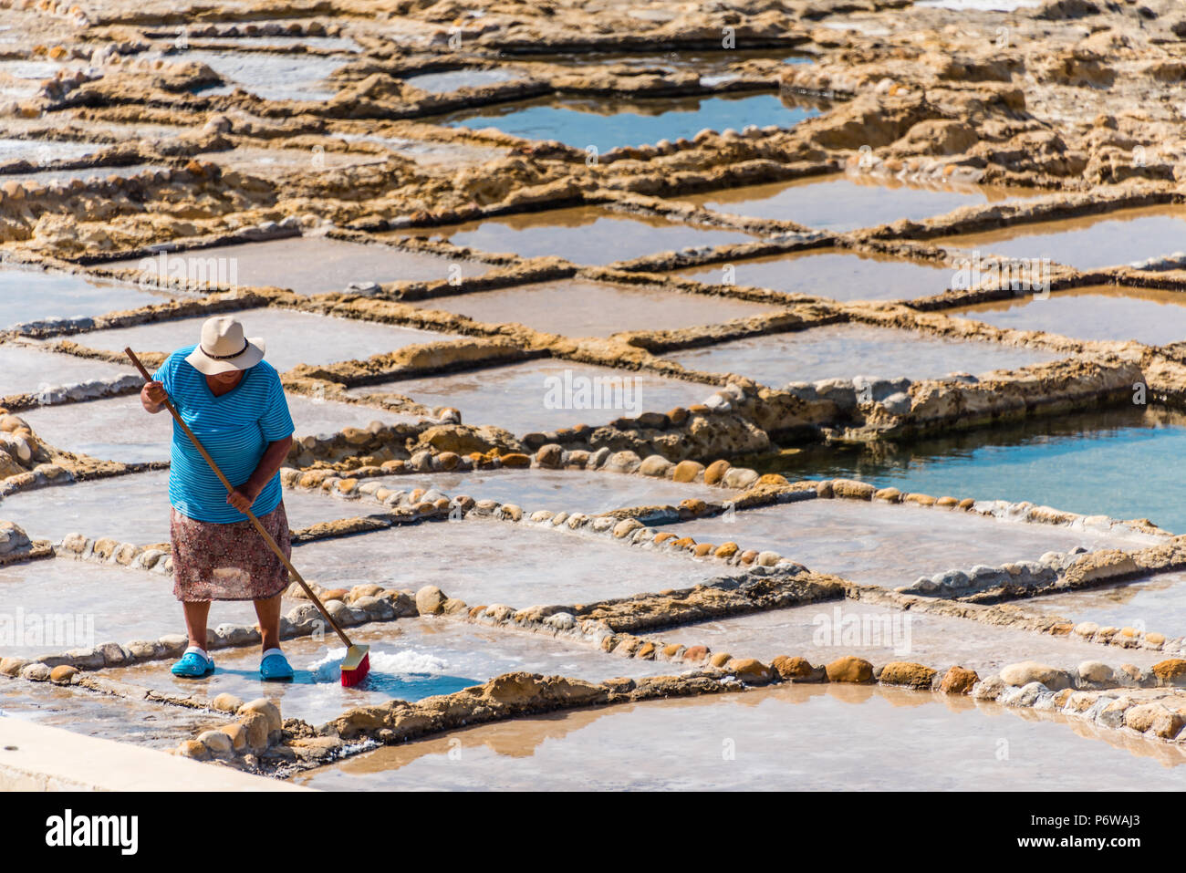 Harvesting sea salt from the ancient salt pans in Marsalforn, Gozo, Malta. - Stock Image