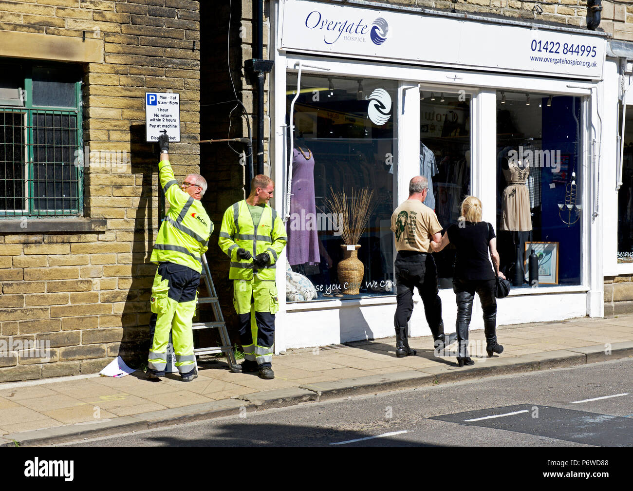 Men putting up signs for new parking restrictions in Hebden Bridge, Calderdale, West Yorkshire, England UK - Stock Image