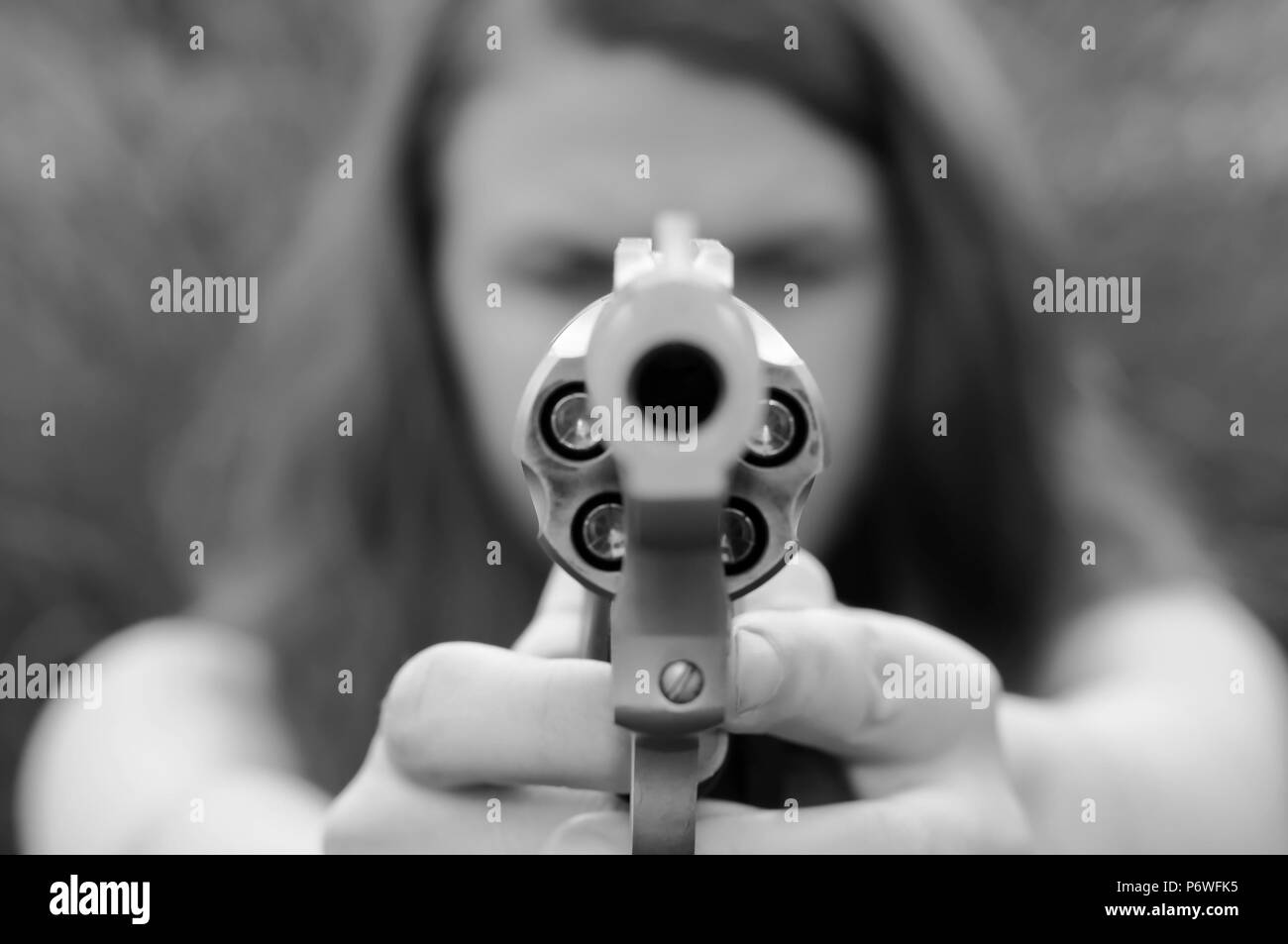 A girl aiming a revolver loaded with hollow point bullets shot in black and white - Stock Image