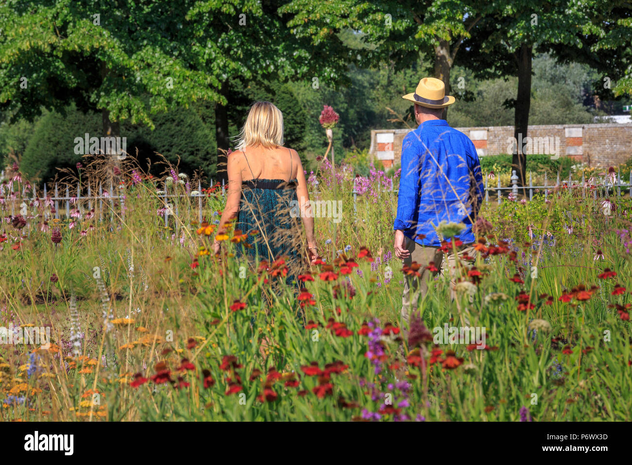 London, UK. 2nd-8th July 2018. RHS Hampton Court Flower Show. Radio DJ Jo Whiley and garden designer and TV celebrity Joe Swift walking in the perennial meadow-style  borders designed by Dutch landscape designer, plantsman and author Piet Oudolf.   - Designer:  Piet Oudolf Stock Photo