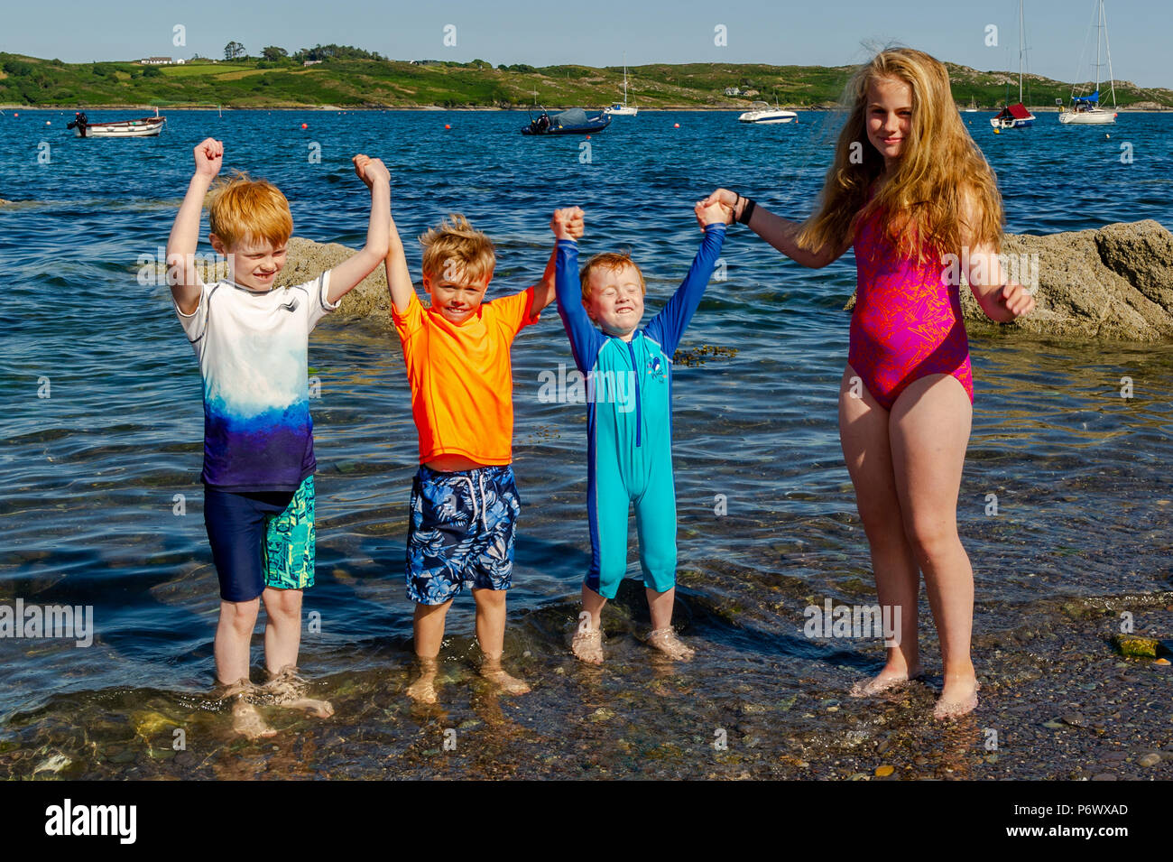 Schull, West Cork, Ireland. 3rd July, 2018. Daniel, Toby, Sam and Eve Enright from Dublin cool off in the sea on another blisteringly hot day. The heatwave shows no sign of ending with temperatures forecast to be in the high 20°'s Celsius for at least a week. Credit: Andy Gibson/Alamy Live News. - Stock Image
