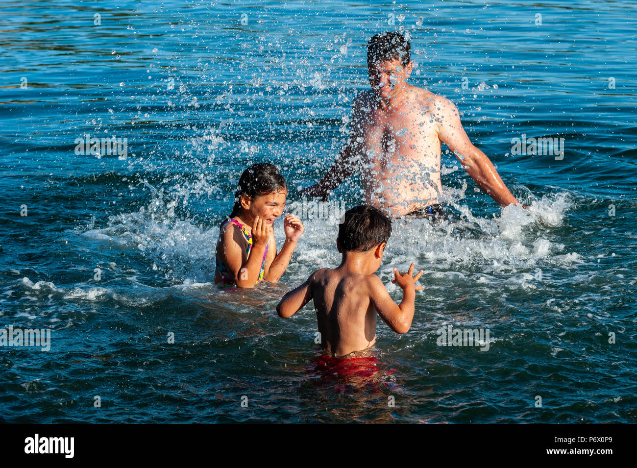 Schull, West Cork, Ireland . Michael O'Driscoll from Ballydehob plays with his children, Hannah, 7 and Patrick, 5, in the sea this evening. The heatwave shows no sign of ending with temperatures forecast to be in the high 20°'s Celsius for at least a week. Credit: Andy Gibson/Alamy Live News. - Stock Image
