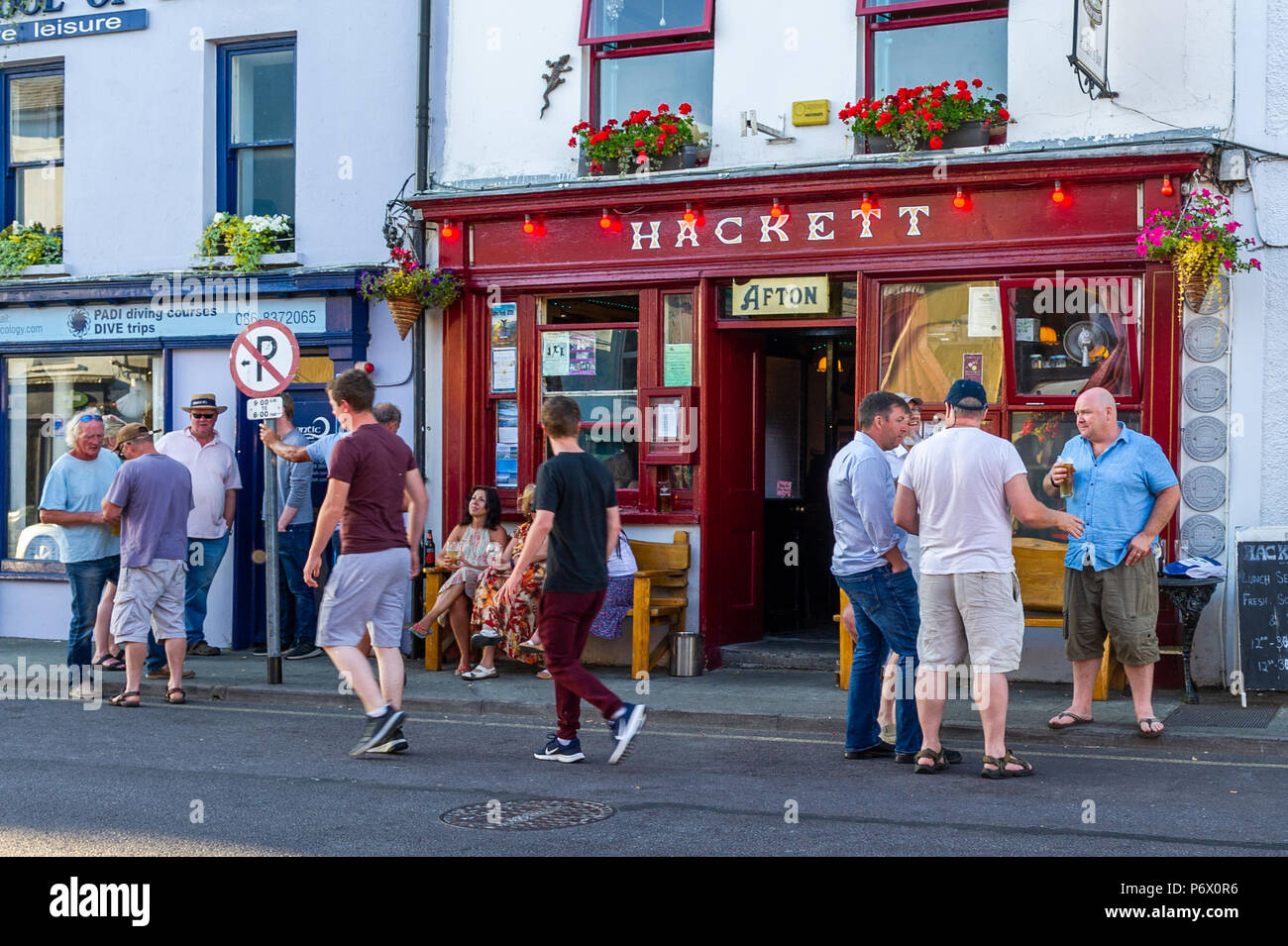 Schull, West Cork, Ireland . Hackett's Bar in Schull Main Street was very busy this evening with locals and tourists alike having a refreshing drink. The heatwave shows no sign of ending with temperatures forecast to be in the high 20°'s Celsius for at least a week. Credit: Andy Gibson/Alamy Live News. - Stock Image