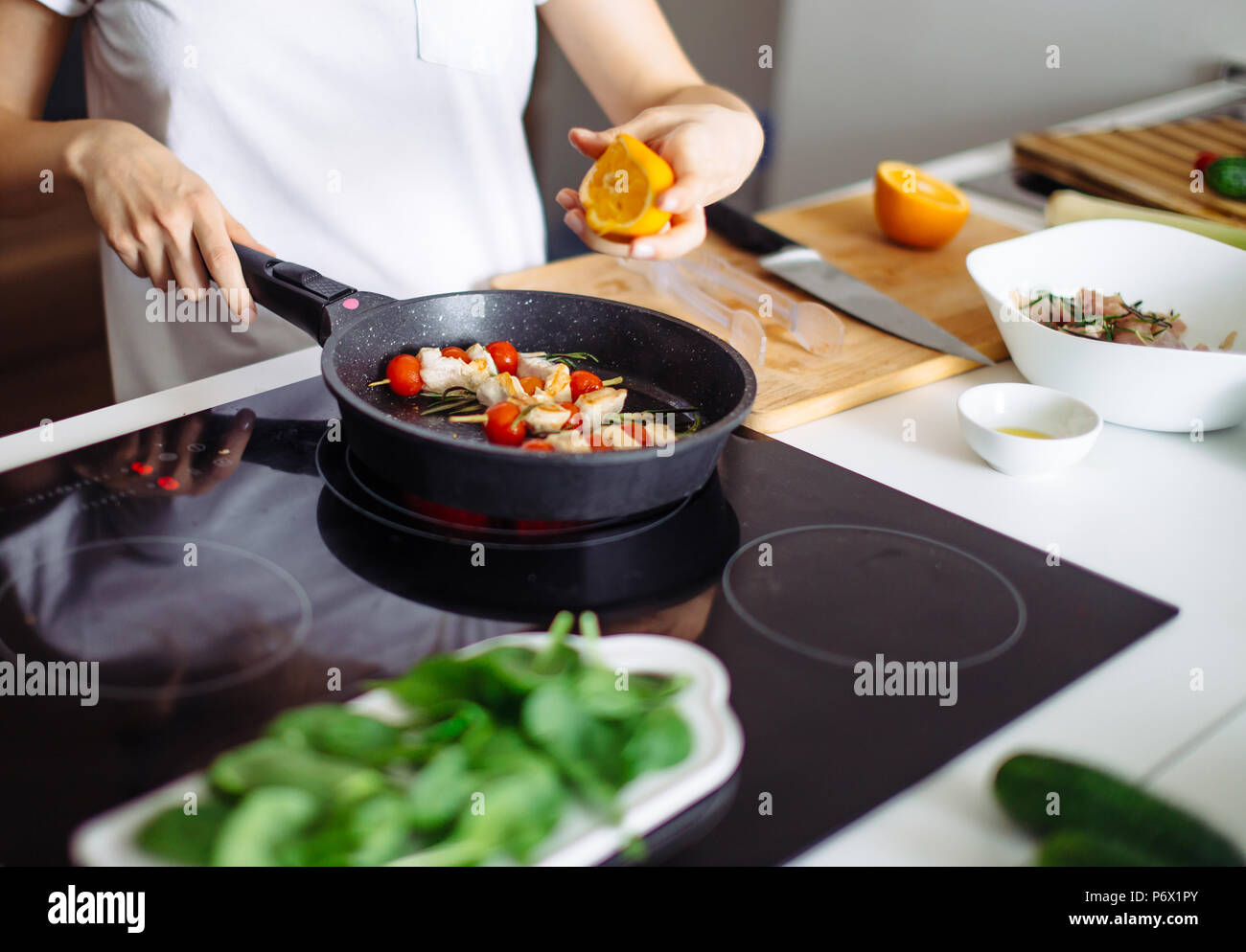 Cropped view of young happy housewife frying chicken meat with orange juice for dinner on glass-ceramic stove. - Stock Image