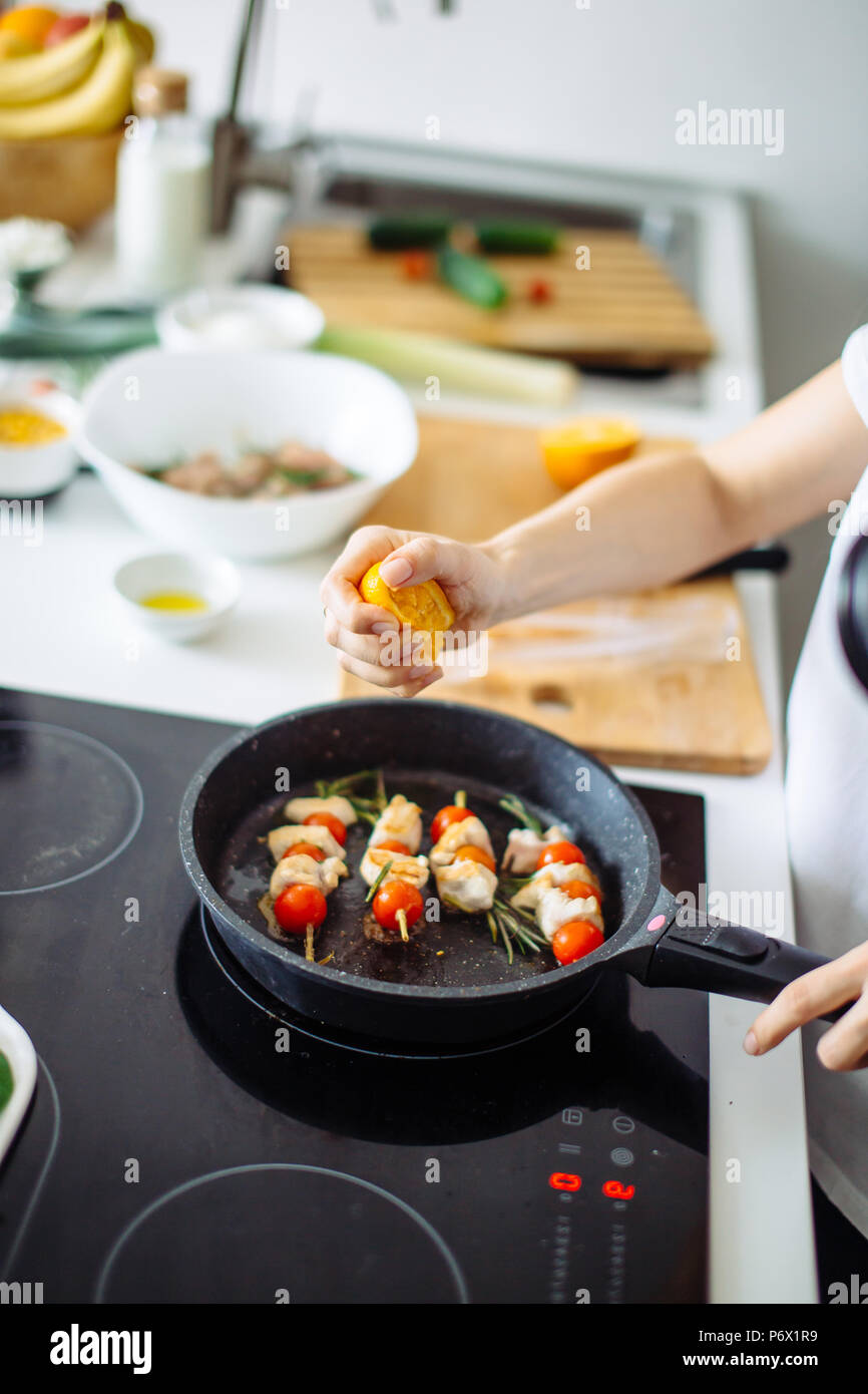 Cropped view of young happy housewife frying chicken meat for dinner on glass-ceramic stove. - Stock Image