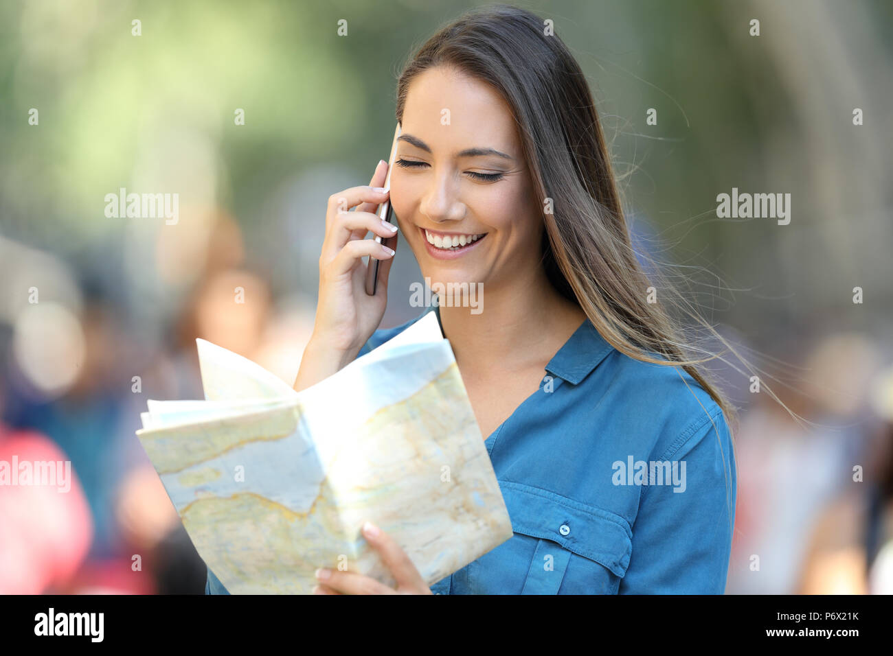 Happy tourist asking information on phone consulting a guide on the street - Stock Image