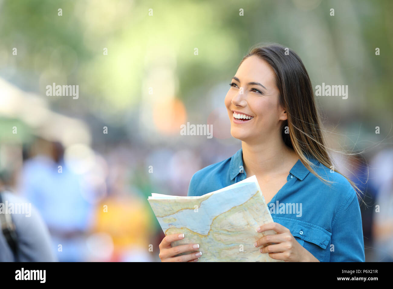 Happy tourist sightseeing and looking at side holding a guide on the street - Stock Image