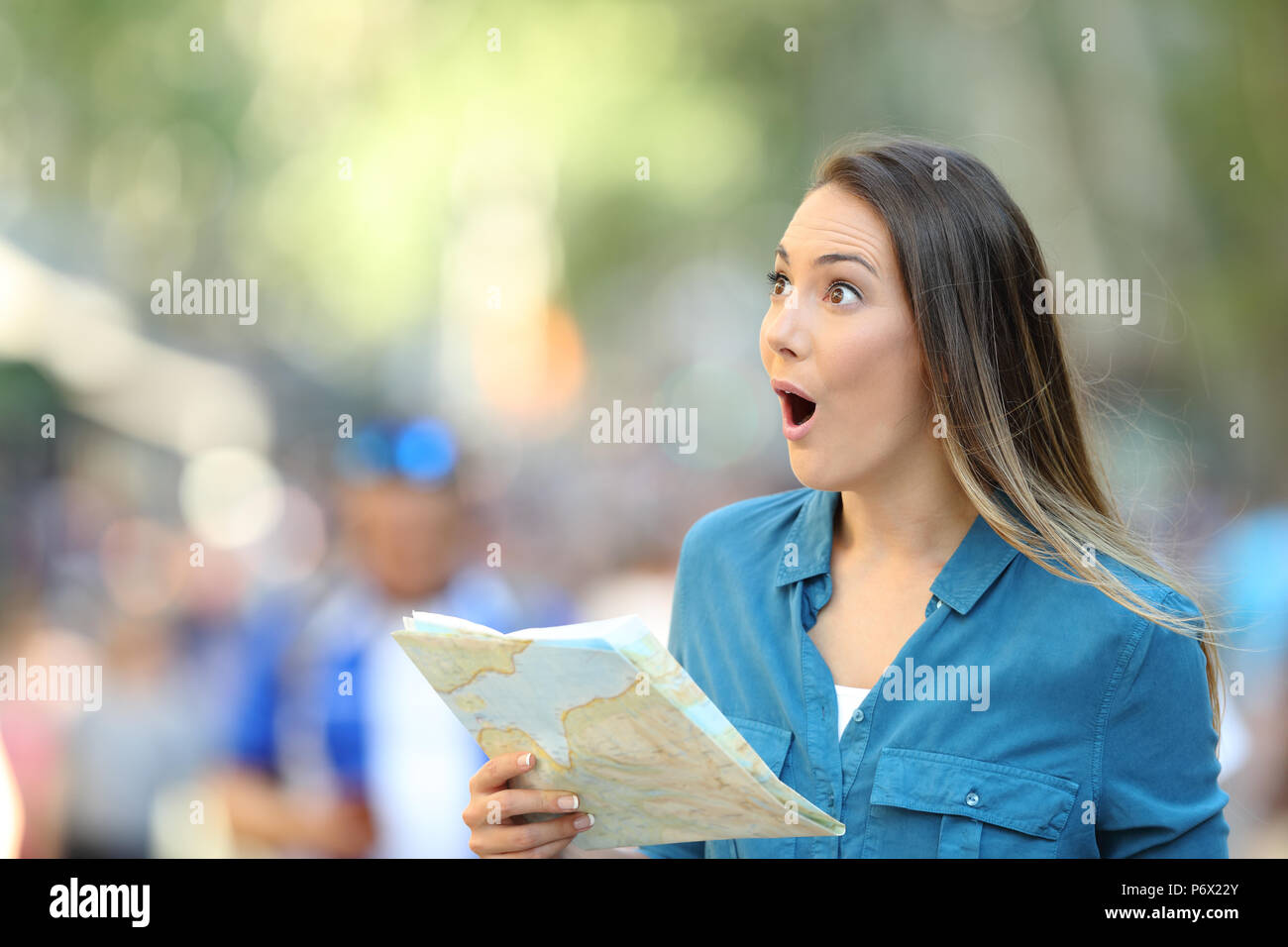Surprised woman sightseeing looking at side holding a map on the street - Stock Image