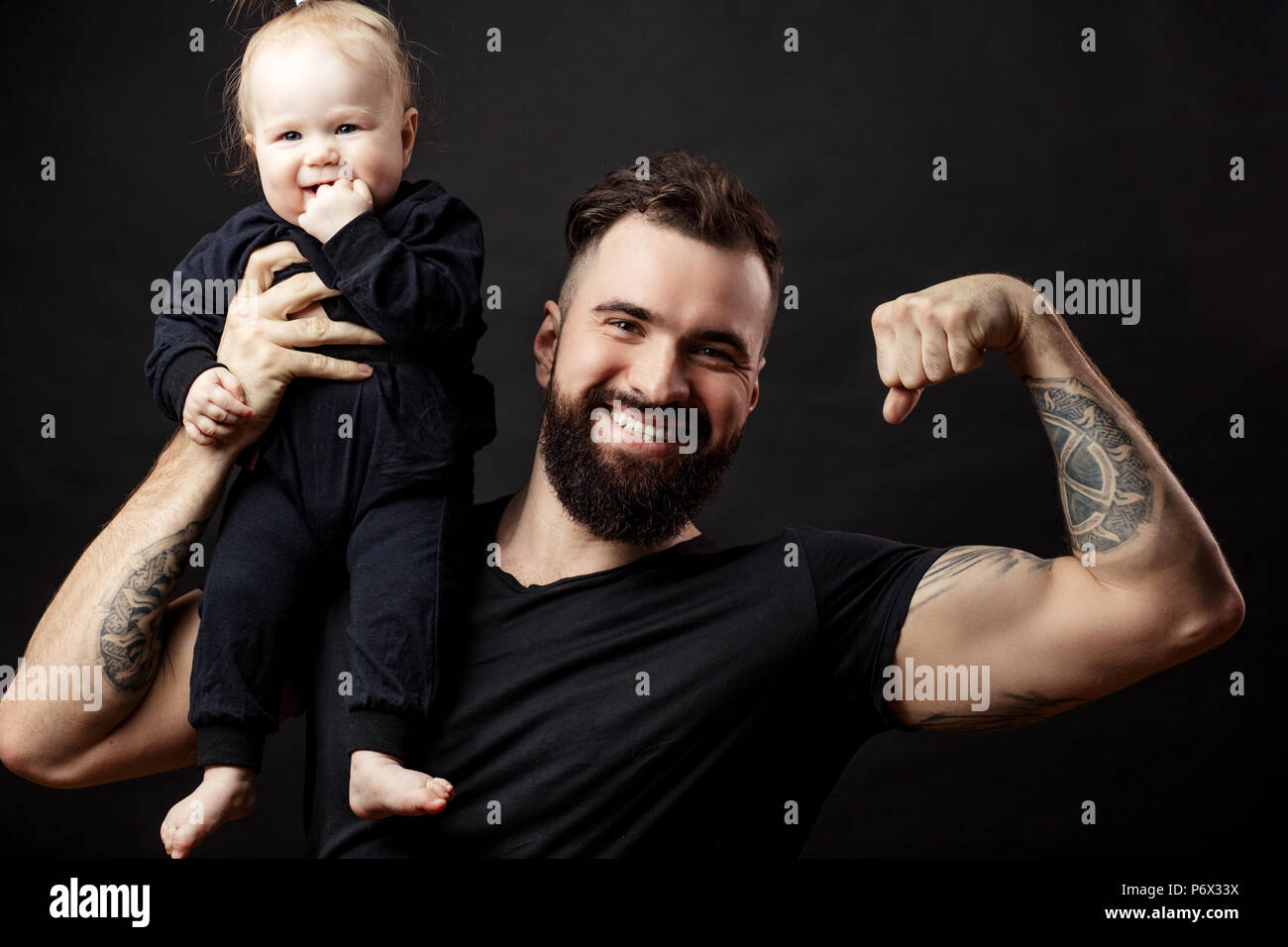 Portrait Of Athletic Well Groomed Handsome Father Holding His Little