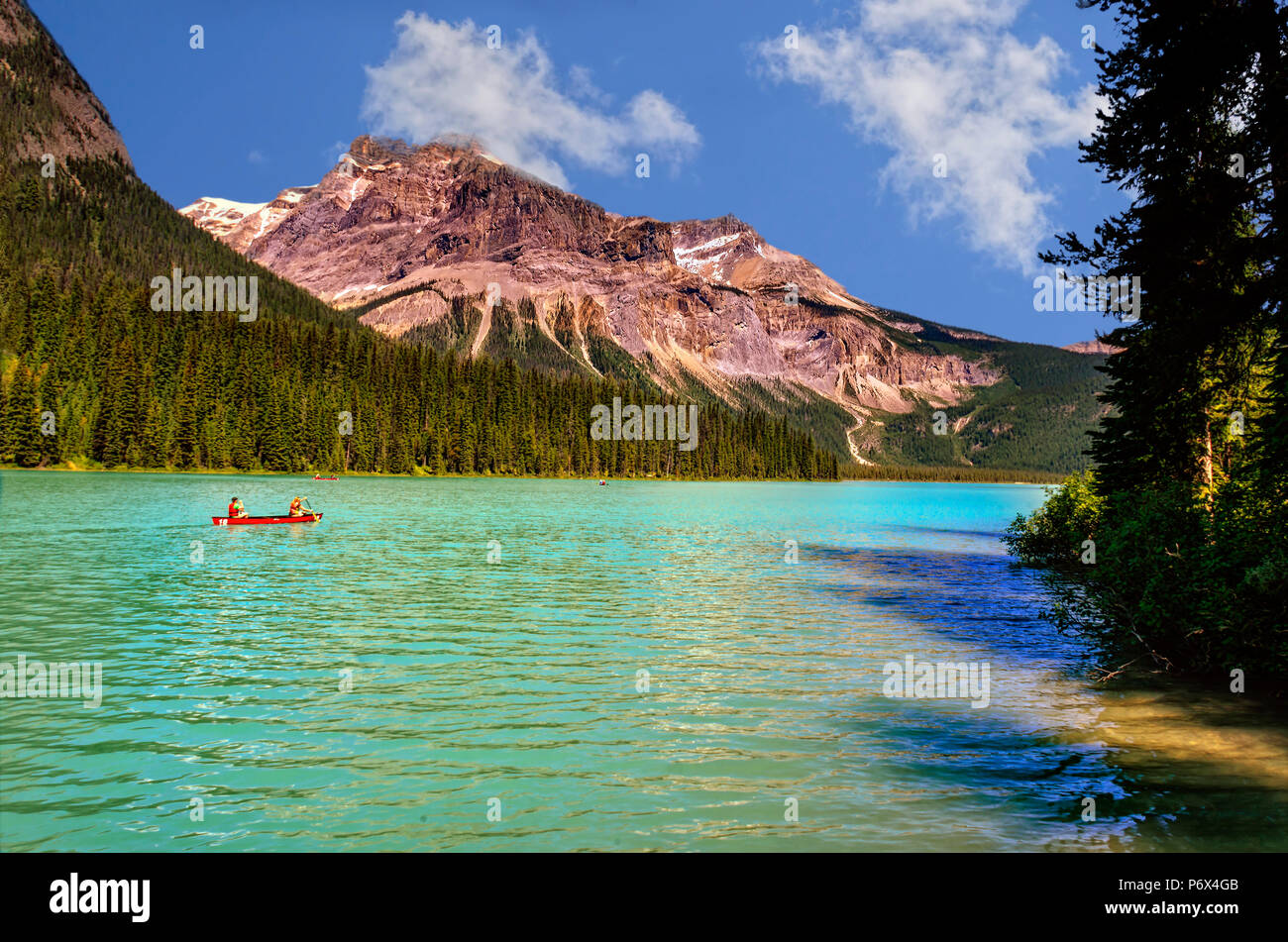 On the emerald green lake, surrounded by coniferous forests and rocky mountains on a bright, sunny day with a blue sky and white clouds, canoeists swi - Stock Image