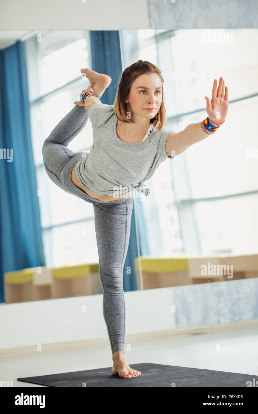 Full length portrait of young fit woman doing a yoga pose standing with one leg raised up. Utthita Hasta Padangusthasana - Stock Image