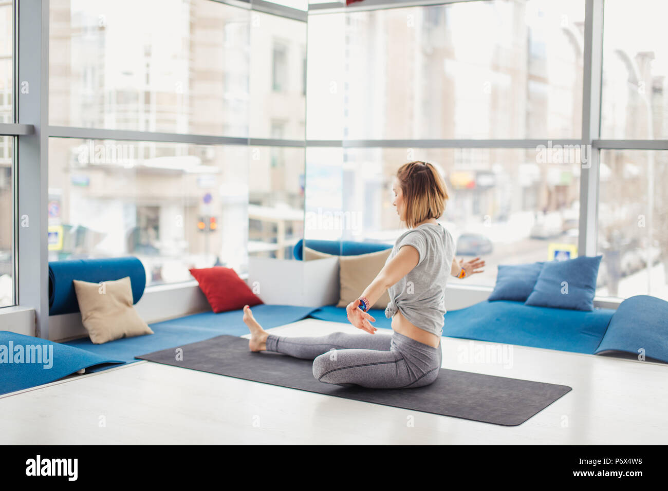 unrecognizable young woman in grey spotrwear working out against big window, doing yoga or pilates exercise. Full length - Stock Image