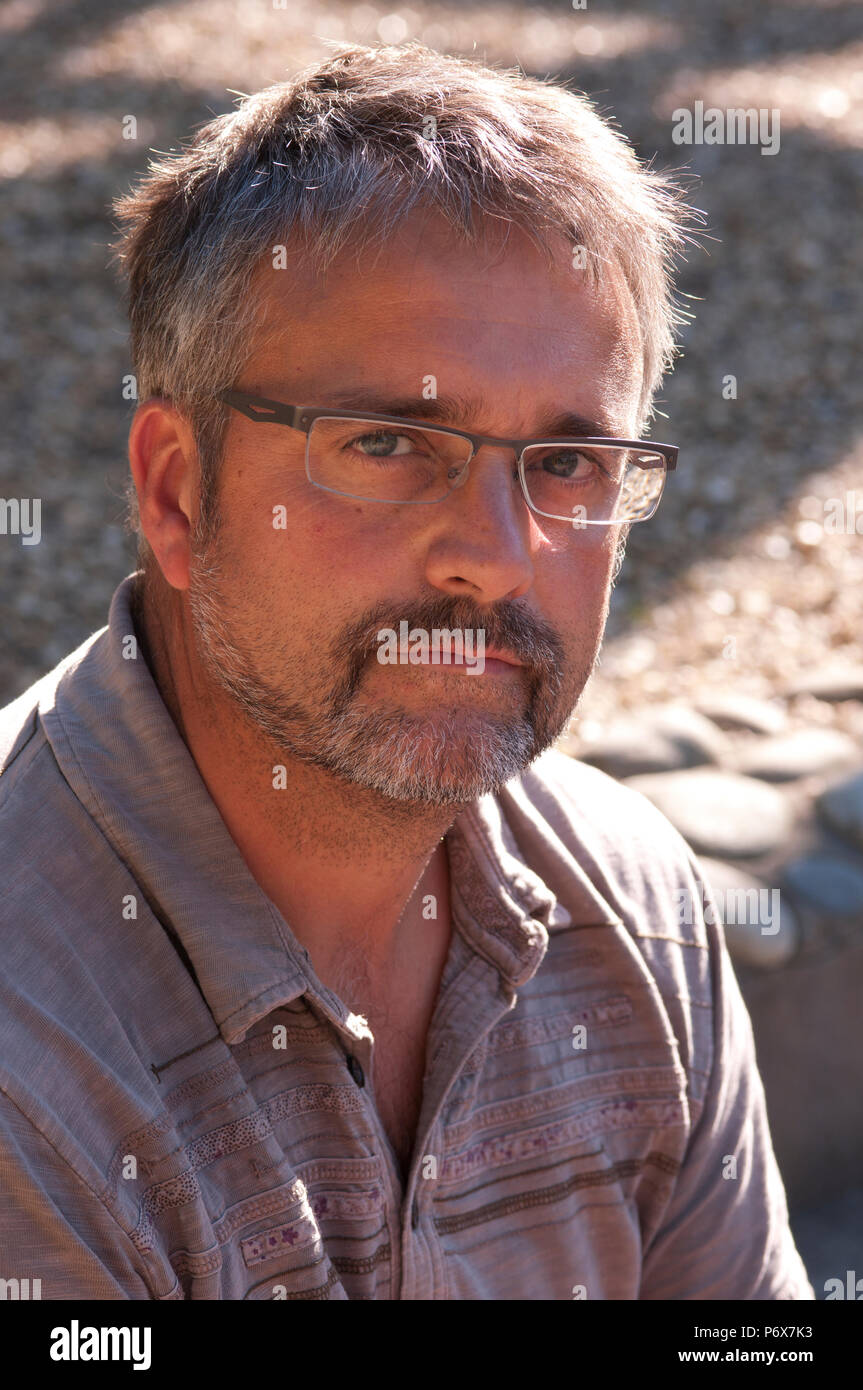 Happy smiling man in his forties wearing glasses - Stock Image