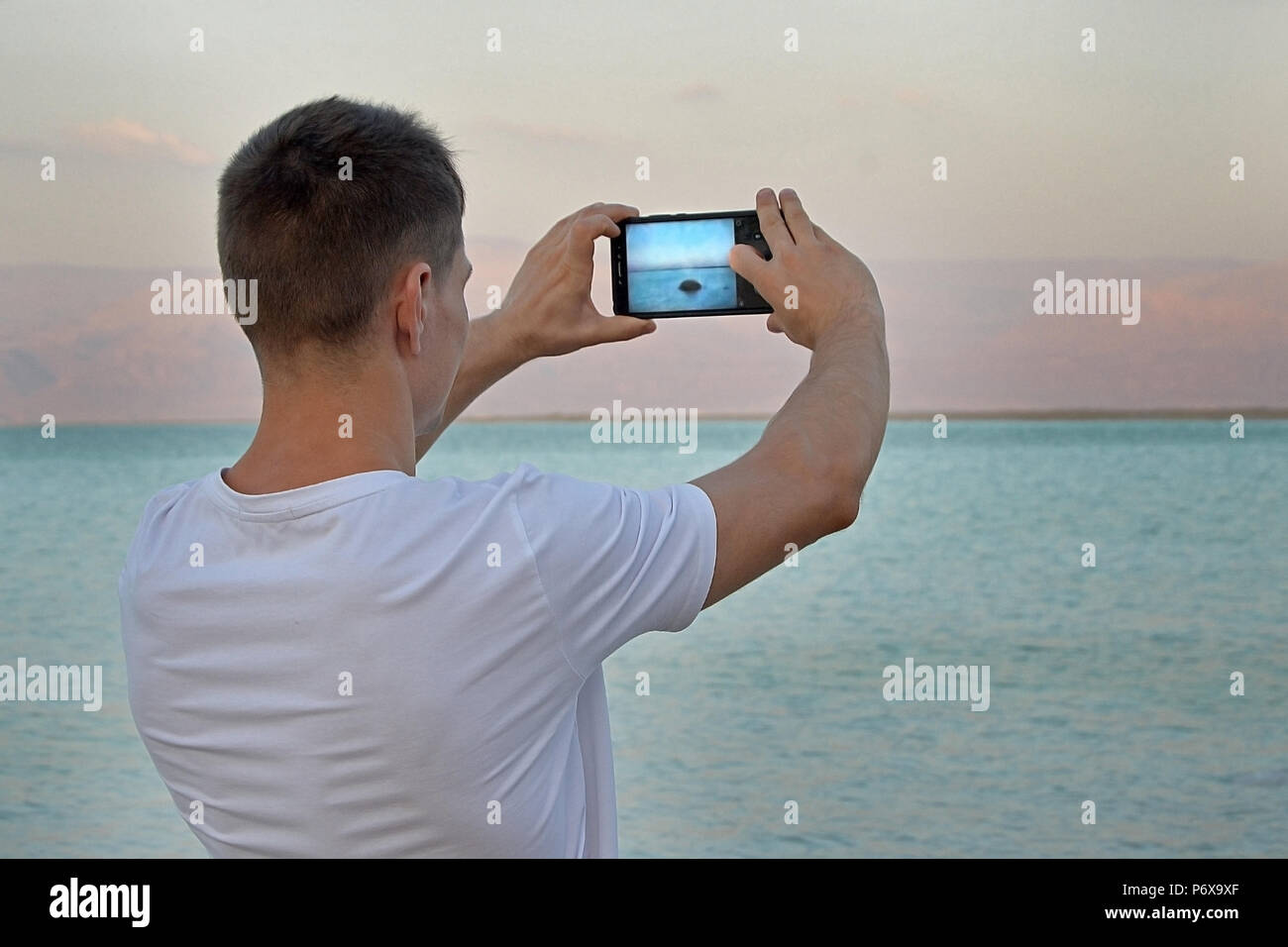 Guy Tourist in a white T-shirt takes pictures using a