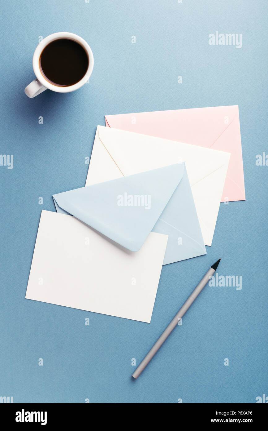 Group of colorful envelopes and a cup of coffee on blue table with empty card. Correspondence concept. Mockup. - Stock Image