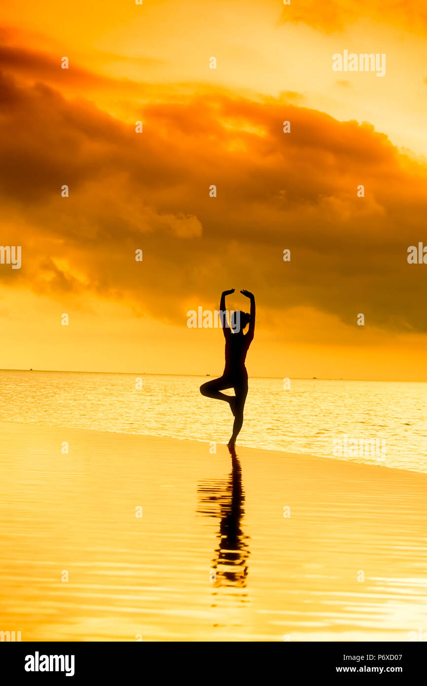 Asia, Cambodia, Sihanoukville, Preah Sihanouk, Koh Rong, Song Saa island resort, woman doing yoga at the edge of a swimming pool against the sunset. MR, PR Stock Photo