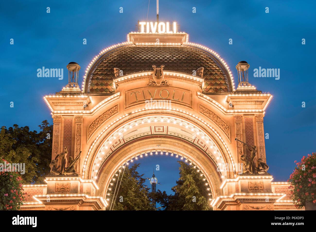 Tivoli gardens, Copenhagen, Hovedstaden, Denmark. The entrance illuminated at dusk. - Stock Image