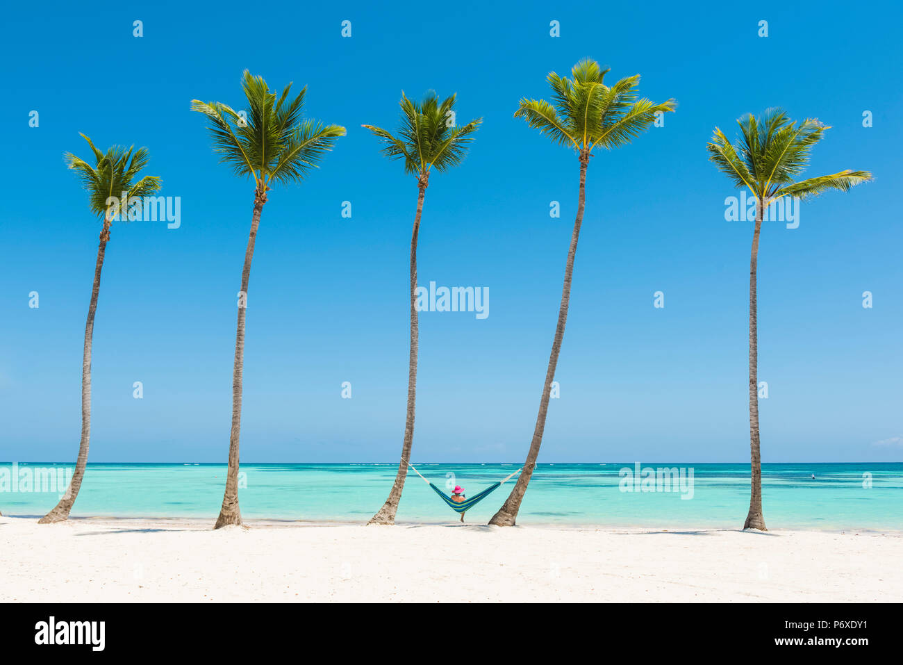 Juanillo Beach (playa Juanillo), Punta Cana, Dominican Republic. Woman relaxing on a hammock on a palm-fringed beach (MR). - Stock Image