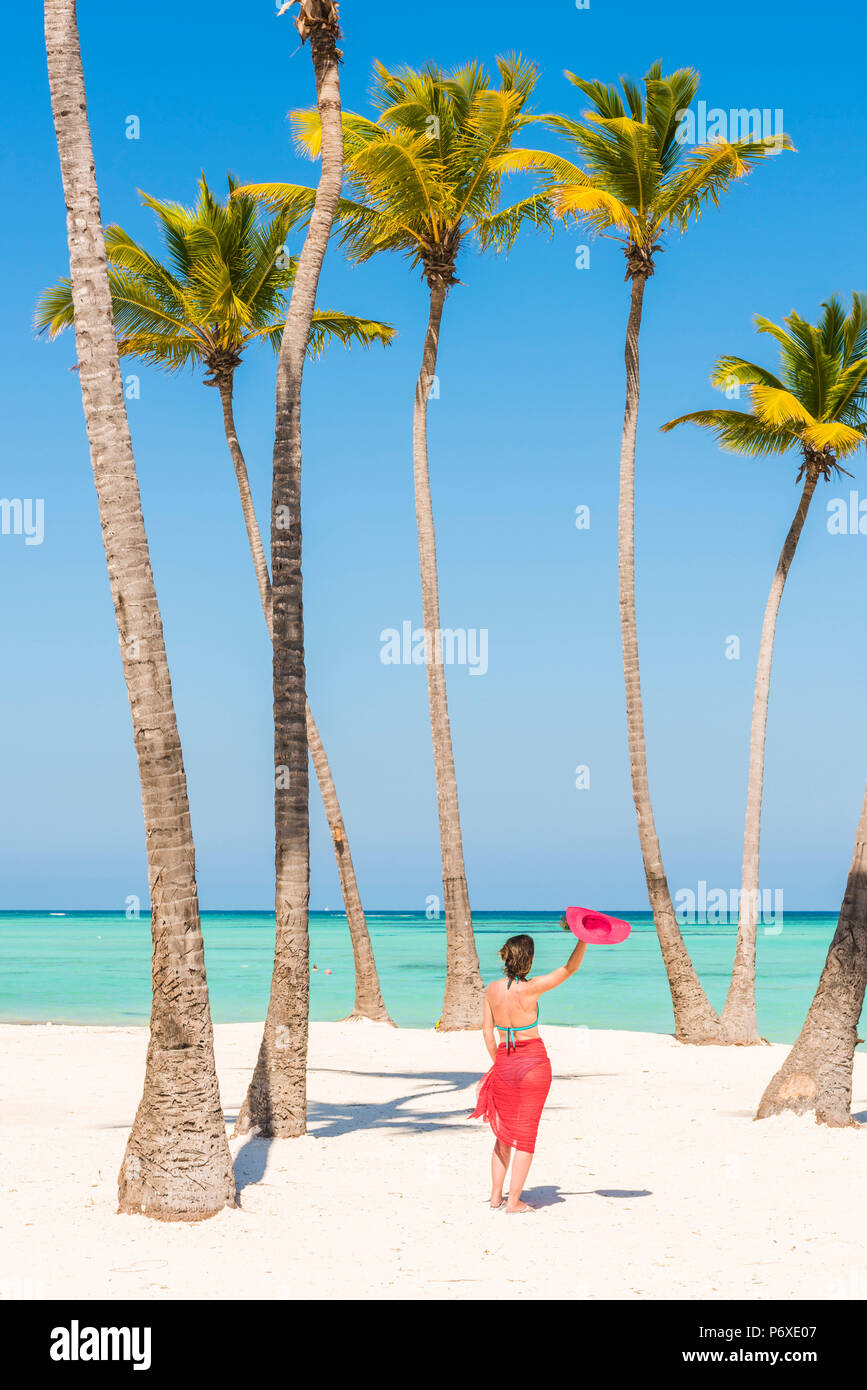 Juanillo Beach (playa Juanillo), Punta Cana, Dominican Republic. Woman relaxing on a palm-fringed beach (MR). - Stock Image