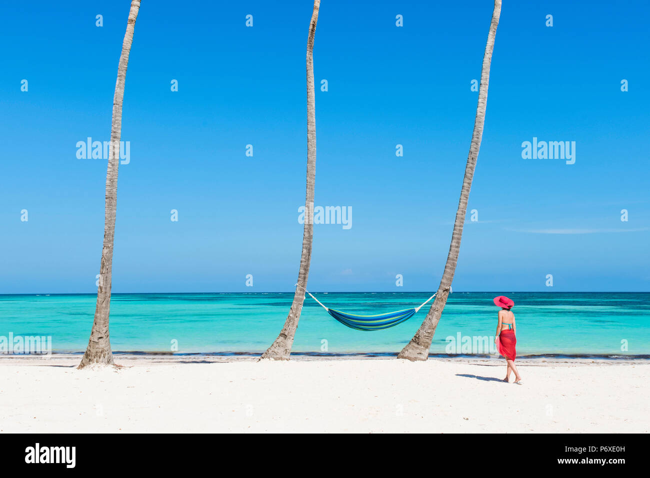 Juanillo Beach (playa Juanillo), Punta Cana, Dominican Republic. Woman walking on a palm-fringed beach (MR). - Stock Image