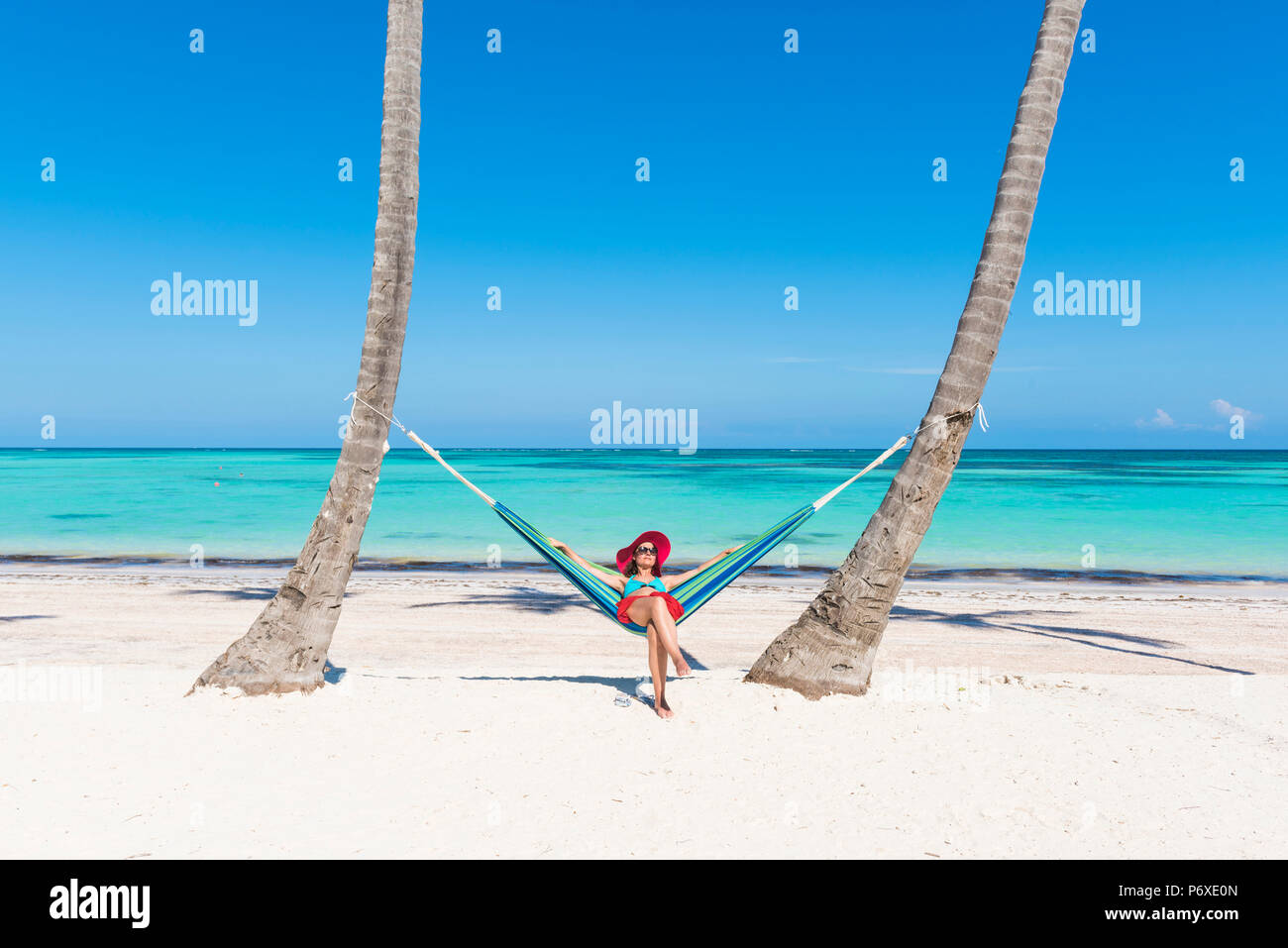 Juanillo Beach (playa Juanillo), Punta Cana, Dominican Republic. Woman relaxing on a hammock on the beach (MR). - Stock Image