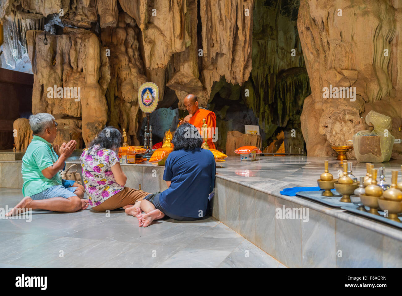 Kanchanaburi, Thailand - May 13, 2018: Group of people making merit by offering things to Buddhist monk in natural cave in Kanchanaburi, Thailand - Stock Image