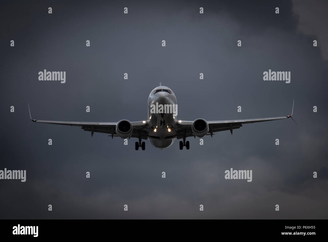 Commercial jetliner on final approach - facing view - Stock Image