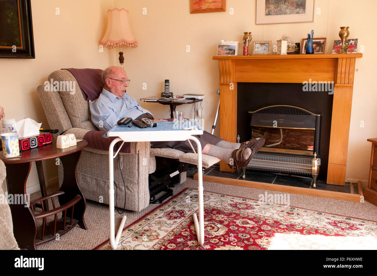 Elderly man snoozing in rise and recline chair - Stock Image