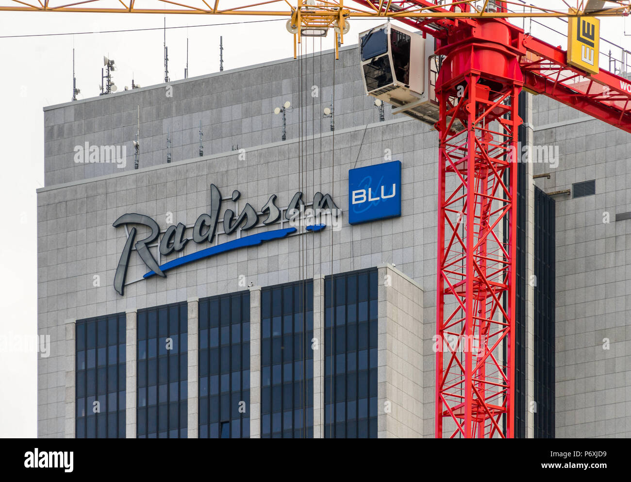 Main building of the Radisson Blu Hotel in Hamburg near the CCH with a construction crane of a construction site in the foreground - Stock Image