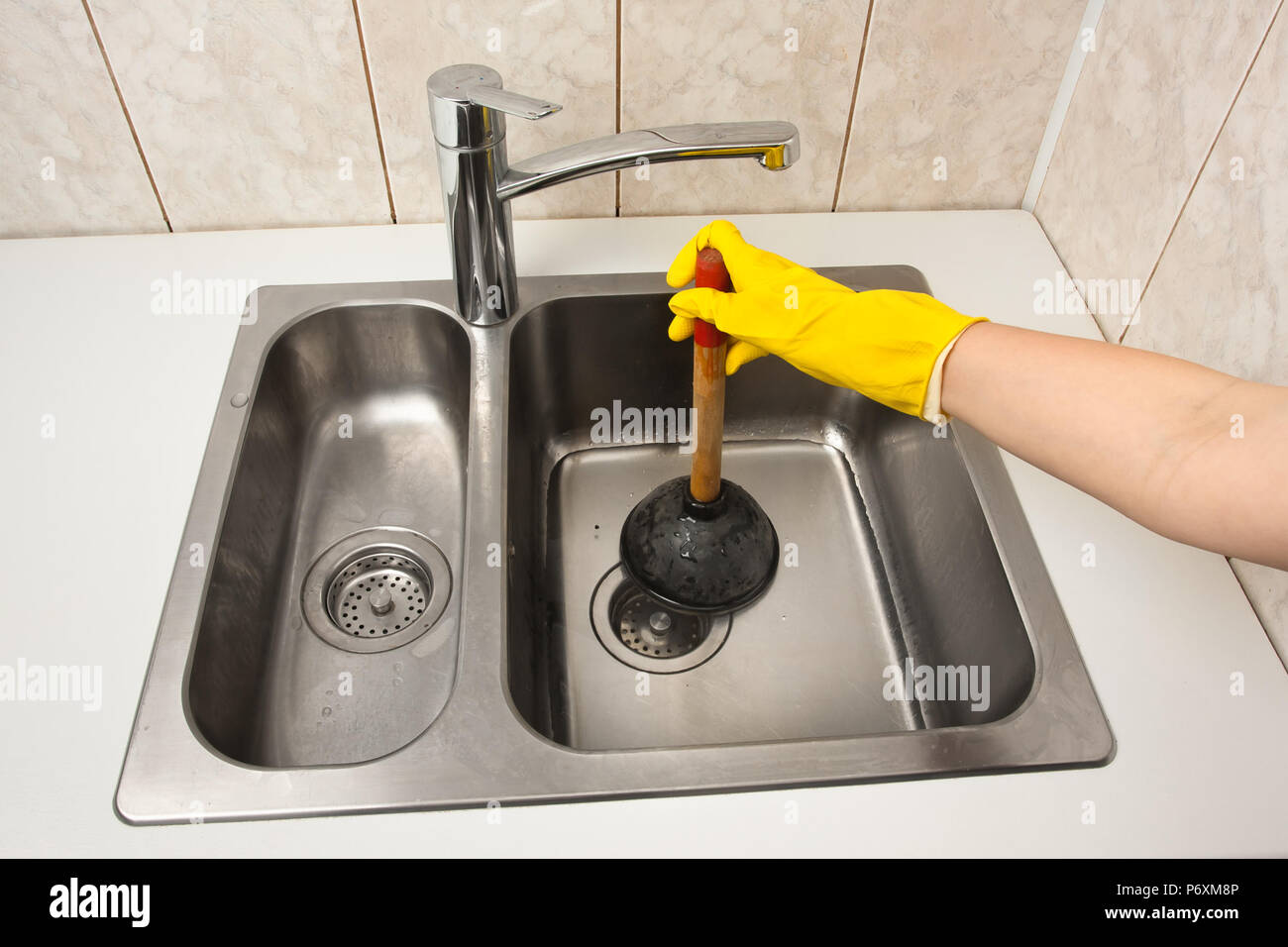 hand using a plunger to cleaning a clogged kitchen sink Stock Photo ...