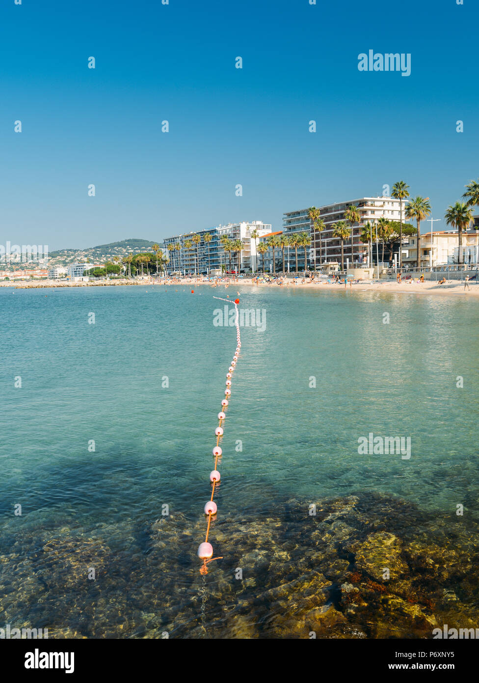 Early morning sun bathers and swimming at the Juan les Pins beach, a popular resort destination on the Mediterranean Stock Photo