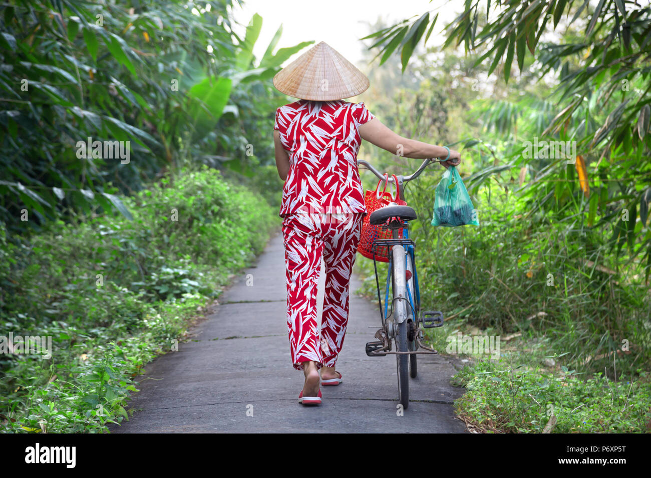 Woman with bicycle and conical hat on An Binh island , Vietnam