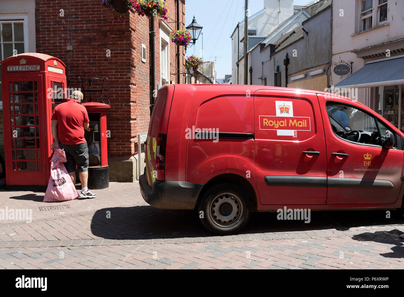 Postal worker emptying a red letterbox in Sidmouth town centre, Devon, UK - Stock Image