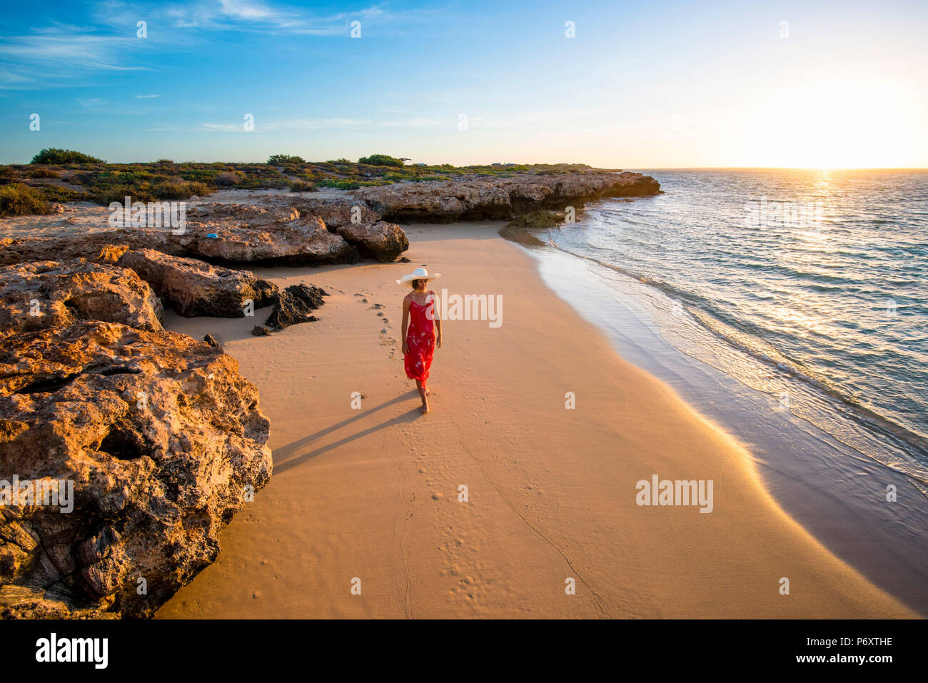 Osprey Bay, Cape Range National Park, Exmouth, Western Australia, Australia. Woman with elegant red dress and straw hat admiring the sunsset (MR). - Stock Image