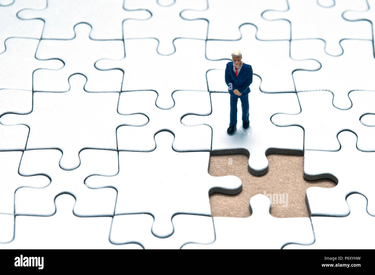 miniature figurine of a businessman standing on a jigsaw puzzle with a missing piece, concept for problem solving and management critical decisions - Stock Image