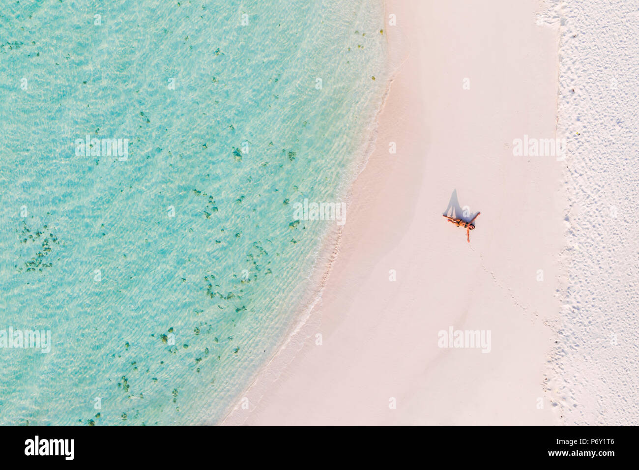 Aerial drone view of woman on a sandy beach, Maldives (MR) - Stock Image