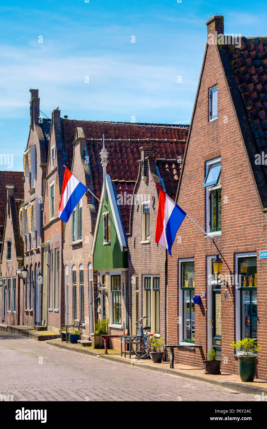 Netherlands, North Holland, Edam. Brick houses with Dutch flags hanging outside for national holiday. - Stock Image