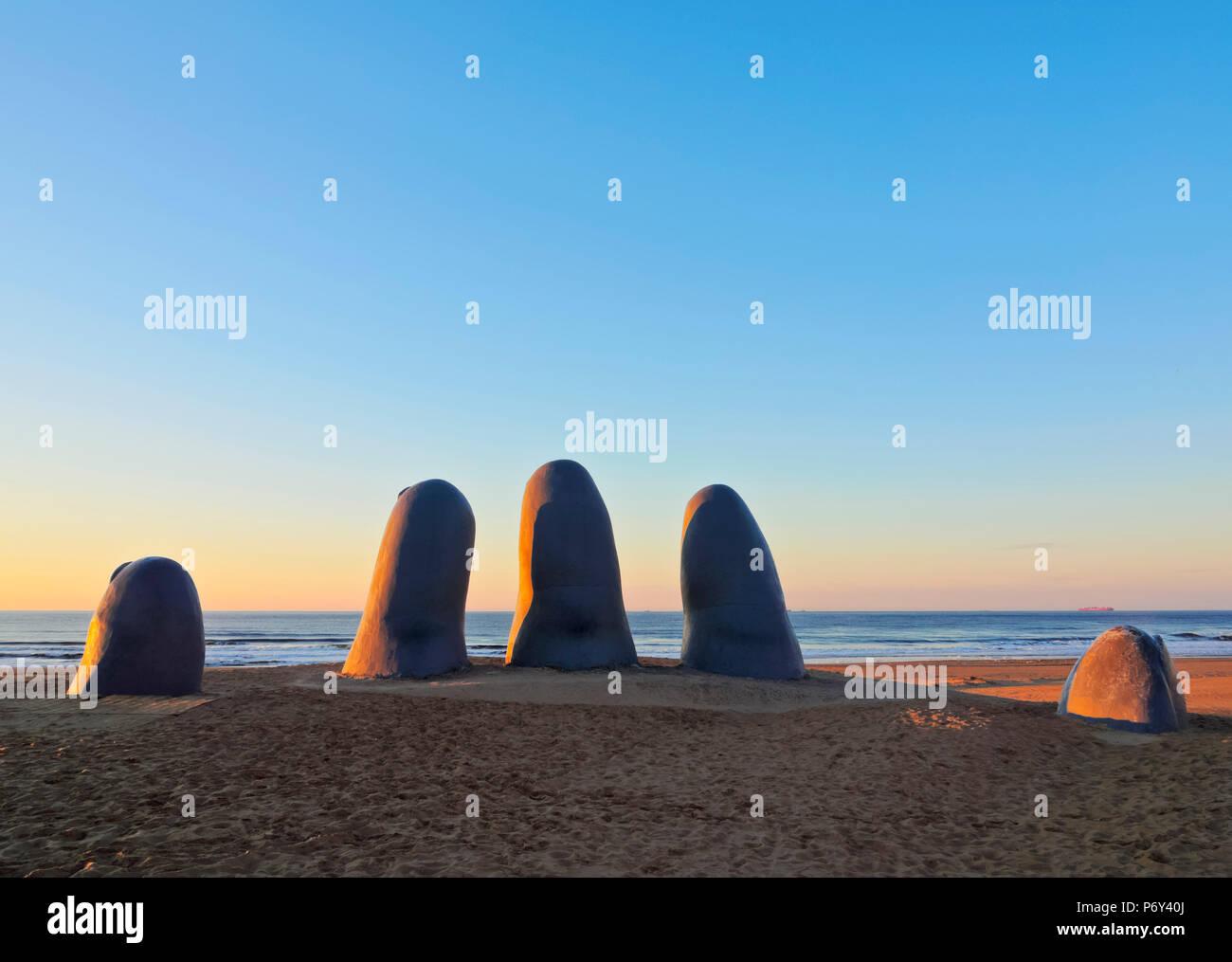 Uruguay, Maldonado Department, Punta del Este, Playa Brava, La Mano(The Hand), a sculpture by Chilean artist Mario Irarrazabal at sunrise. - Stock Image