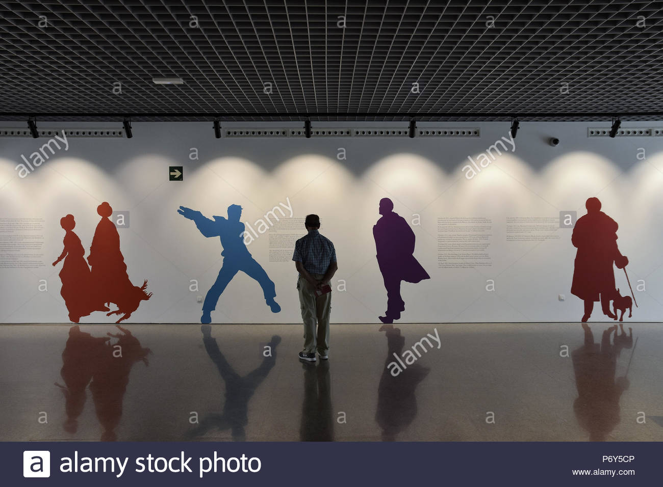 Visitor standing by the wall with painted outline figures from Russian history. Museo Ruso (Russian Museum) in Malaga Spain Europe. - Stock Image
