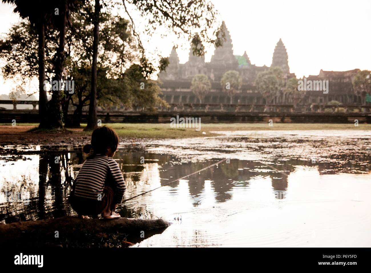 Girl fishing in the lake of Angkor Wat, ancient Cambodian city hidden in the forest very visited by tourists - Stock Image
