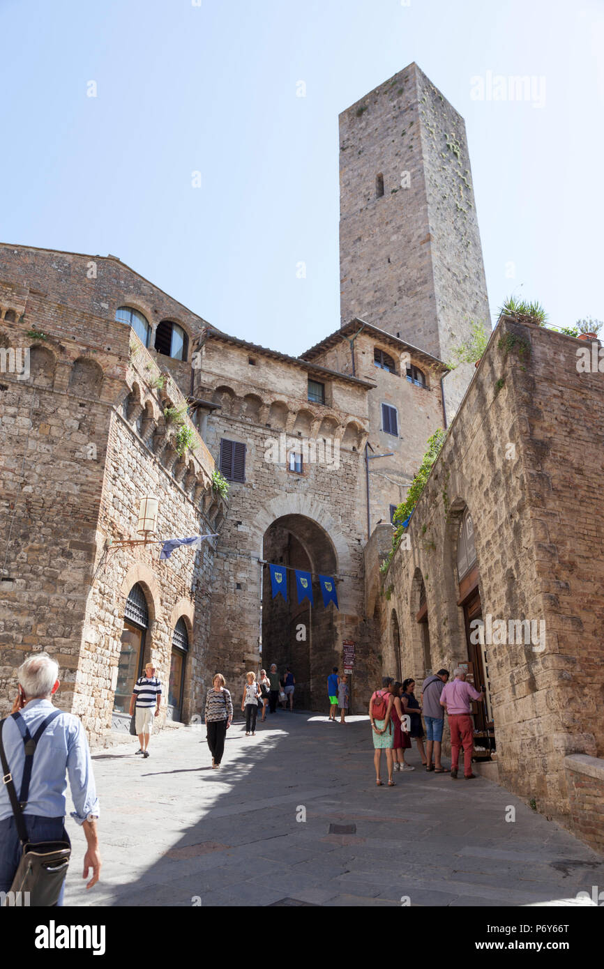 The San Giovanni street, at Gimignano (Tuscany - Italy). The St Gimignano's crowdy main street of tourists has received its name from the eponym door. Stock Photo